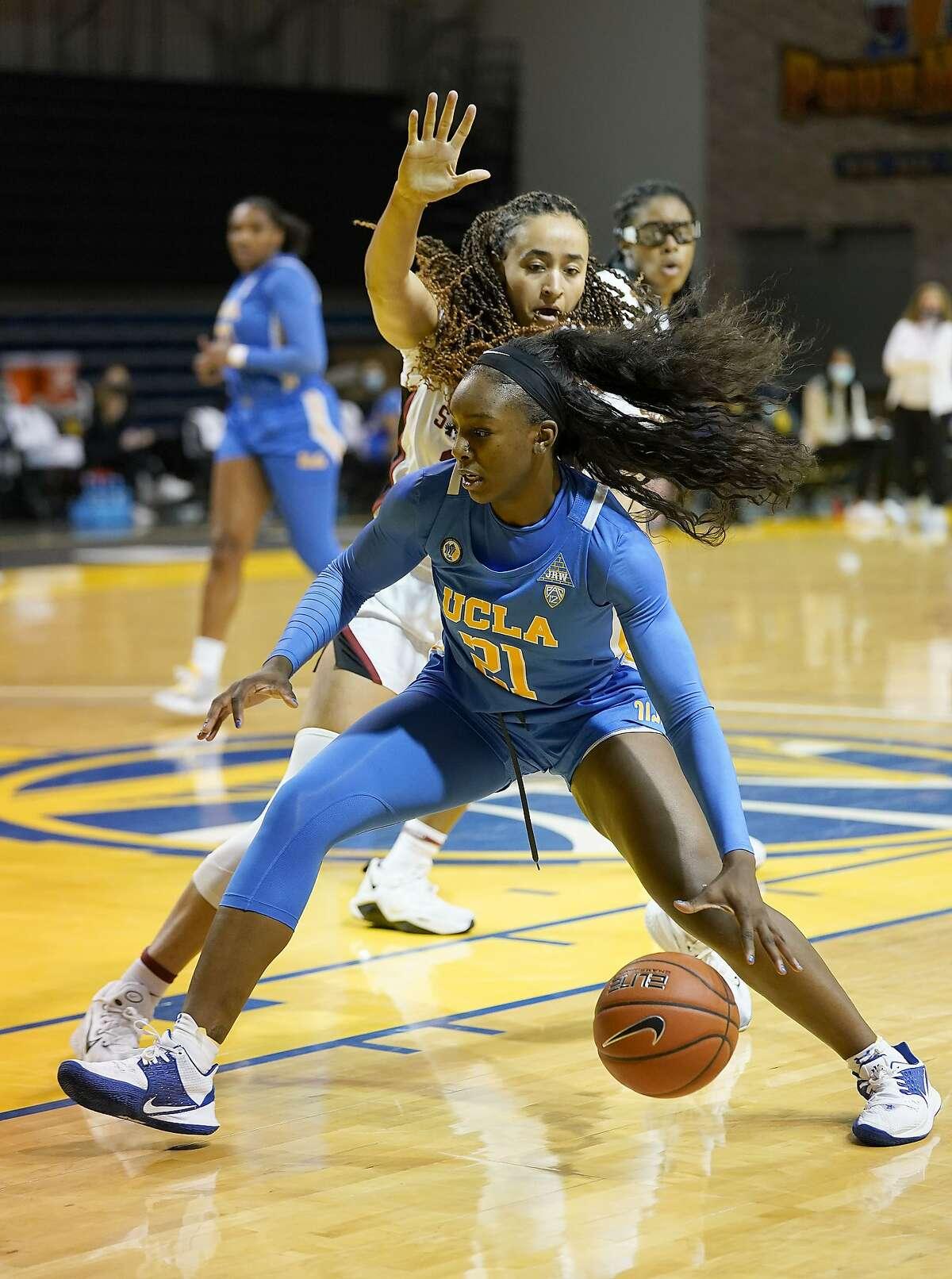 UCLA forward Michaela Onyenwere (21) drives with the ball against Stanford guard Haley Jones (30) during the first half of an NCAA college basketball game in Santa Cruz, Calif., Friday, Jan. 22, 2021. (AP Photo/Tony Avelar)