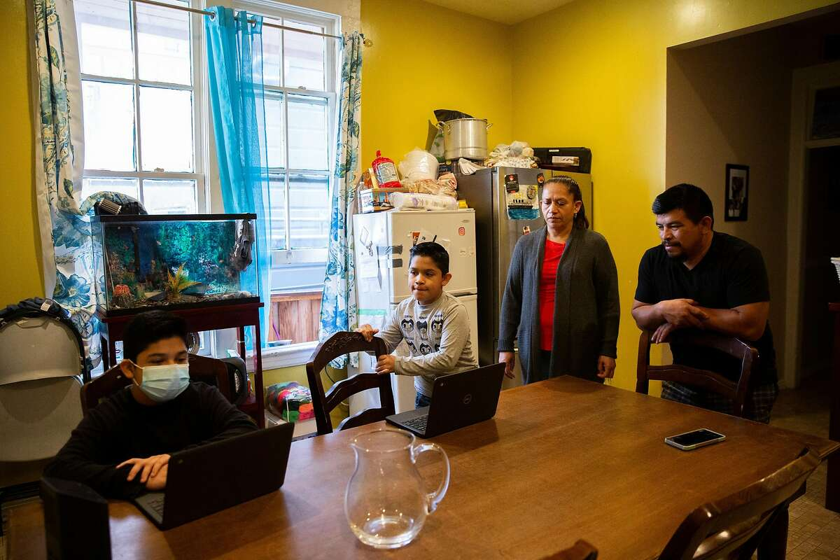 Thirteen-year-old Nelvin Lopez Velasquez (left) and brother Carlos Lopez Velasquez, 9, do their homework on their school laptops as mother Antonia Lopez and father Nelvin Velasquez watch over them. The family has been living in a Mission District apartment for more than a decade. Nelvin, a handyman, isolated after testing positive for the coronavirus. He has since recovered and lost a majority of his work because of the pandemic. The family is behind more than $6,000 on rent, and debt continues to pile up.