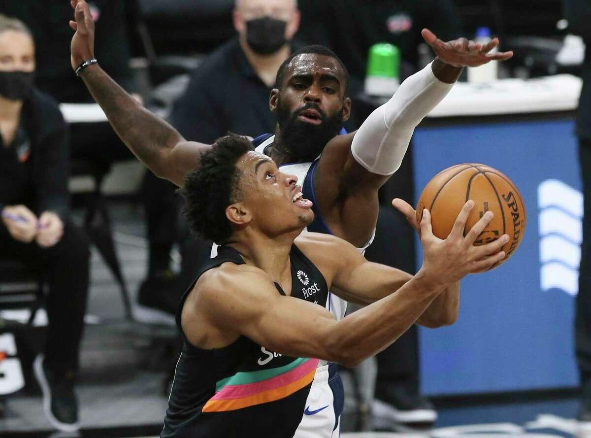 Spurs' Keldon Johnson (03) goes strong to the basket against Dallas Mavericks' Tim Hardaway Jr. (11) at the AT&T Center on Friday, Jan. 22, 2021.