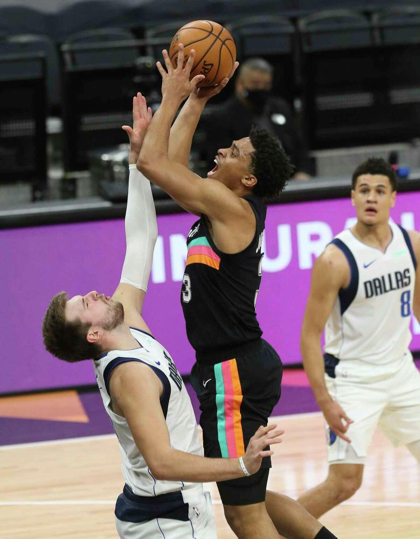Spurs' Keldon Johnson (03) shoots against Dallas Mavericks' Luka Doncic (77) at the AT&T Center on Friday, Jan. 22, 2021.