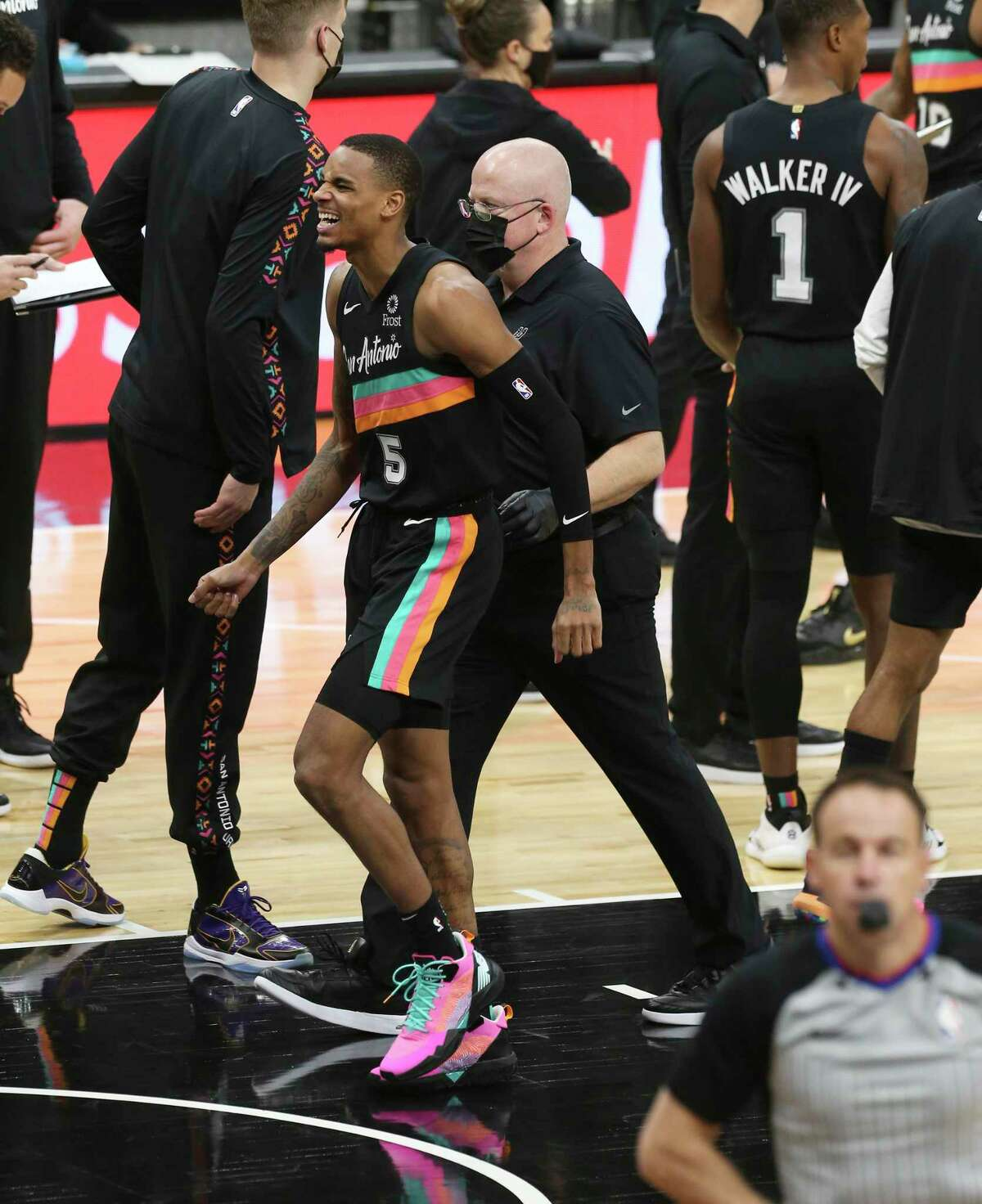 Spurs' Dejounte Murray (05) winces in pain as he heads to the locker room after getting his left foot stepped on by Dallas Mavericks' Kristaps Porzingis (06) at the AT&T Center on Friday, Jan. 22, 2021.