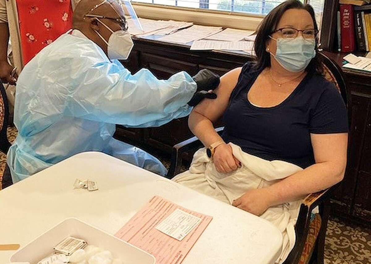 Kelly Allen, executive director for Elmcroft at Cy-Fair, rolls up her sleeve and takes the first-round vaccination for the Covid-19 virus. Allen said she wanted to be an example for her residents and staff and had no problems taking the vaccine.