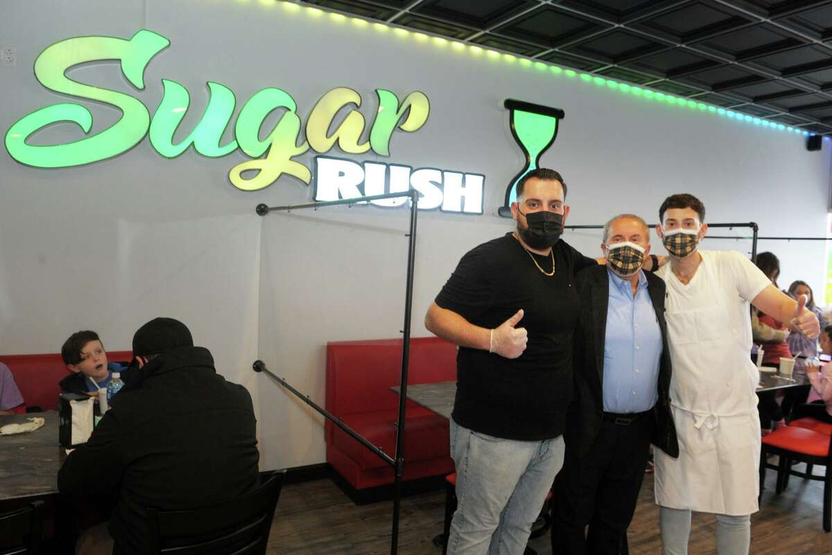 Owner Remzi Nasufi, center, poses with his sons and managers Ali, left, and Flamur at Sugar Rush, a new ice cream shop in Shelton, Conn. Jan. 18, 2021.