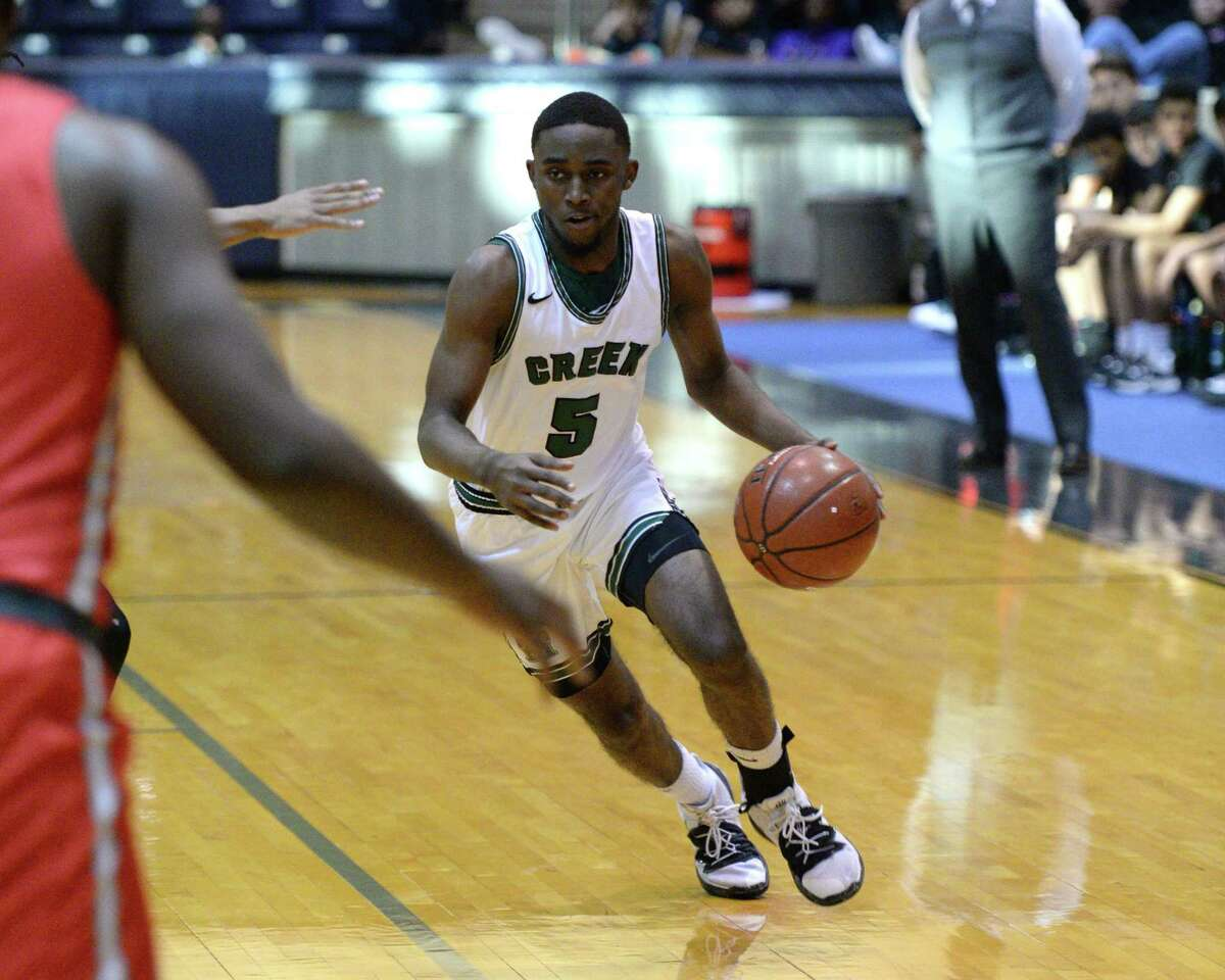 Jermon Washington (5) of Mayde Creek dribbles toward the paint during the first quarter of a Boys 6A Region III Bi-District play-off game between the Mayde Creek Rams and the Travis Tigers on Tuesday, February 25, 2020 at Coleman Coliseum, Houston, TX.