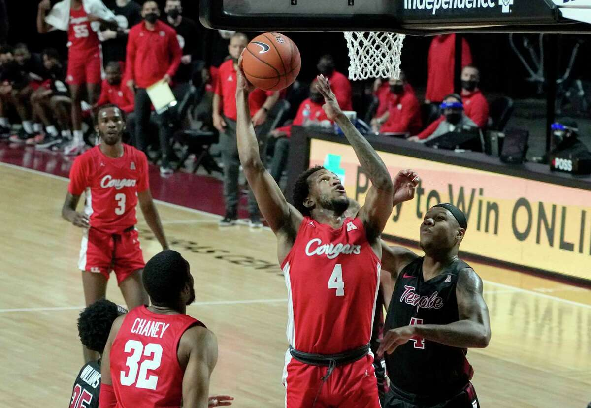 Houstons's Justin Gorham (4) takes a shot over Temple's J.P. Moorman II (4) in the first half of an NCAA college basketball game, Saturday, Jan. 23, 2021, in Philadelphia. (AP Photo/Michael Perez)