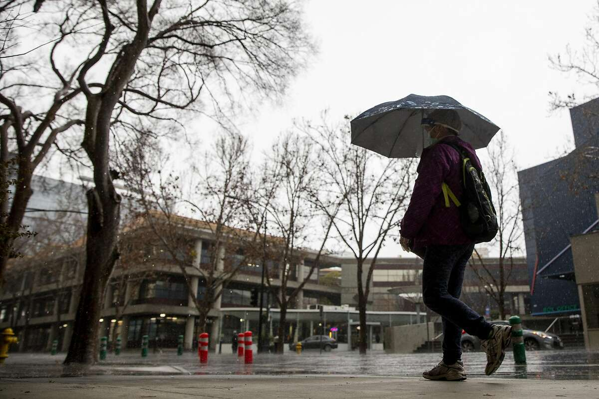 A person wears a mask and face shield while carrying an umbrella on South 3rd Street as rain falls in downtown San Jose on Friday. Rain is expected to return Sunday.