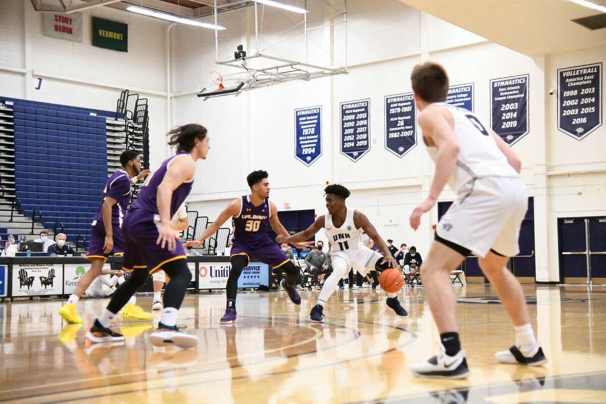 New Hampshire's Blondeau Tchoukuiengo is surrounded by UAlbany defenders (clockwise from front) Cameron Healy, Jarvis Doles and Chuck Champion in the first half of an America East basketball game Saturday, Jan. 23, 2021, at Lundholm Gymnasium in Durham, N.H. (Larissa Biette/UNH athletics)