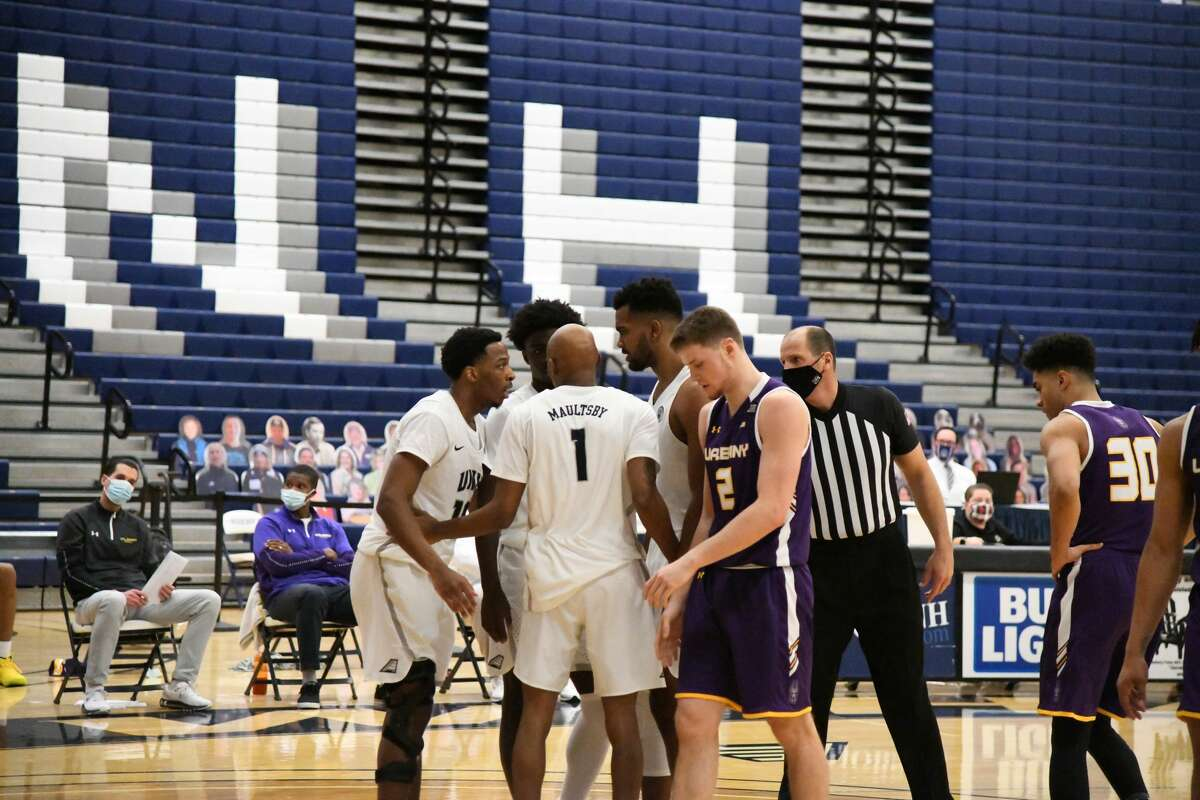 UAlbany's Trey Hutcheson (2) and Chuck Champion (30) walk dejectedly as New Hampshire players gather after a foul call against the Danes in the first half of an America East basketball game Saturday, Jan. 23, 2021, at Lundholm Gymnasium in Durham, N.H. (Larissa Biette/UNH athletics)