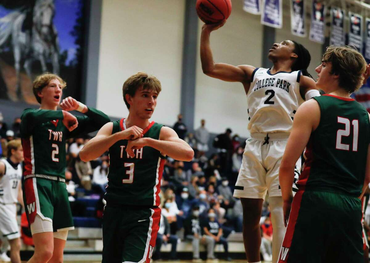 The Woodlands guards Hagen Byerly (3) and Sheyy Eberwein (2) signal for a traveling call agaisnt College Park guard Marvin Dock (2) during the first quarter of a Districrt 15-6A high school basketball game at College Park High School, Saturday, Jan. 23, 2021, in The Woodlands.