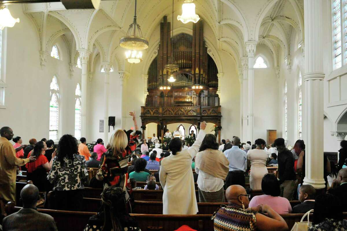 """Congregation members stand to pray during Easter Sunday service at Albany's Sweet Pilgrim Missionary Baptist Church in 2015. On Monday, Jan. 25, the church will be the site of a state deployment of community coronavirus vaccination kits, part of an effort that Gov. Andrew M. Cuomo's office said will """"strengthen fairness and equity in the vaccine distribution process."""" (Times Union archive) (Paul Buckowski / Times Union)"""