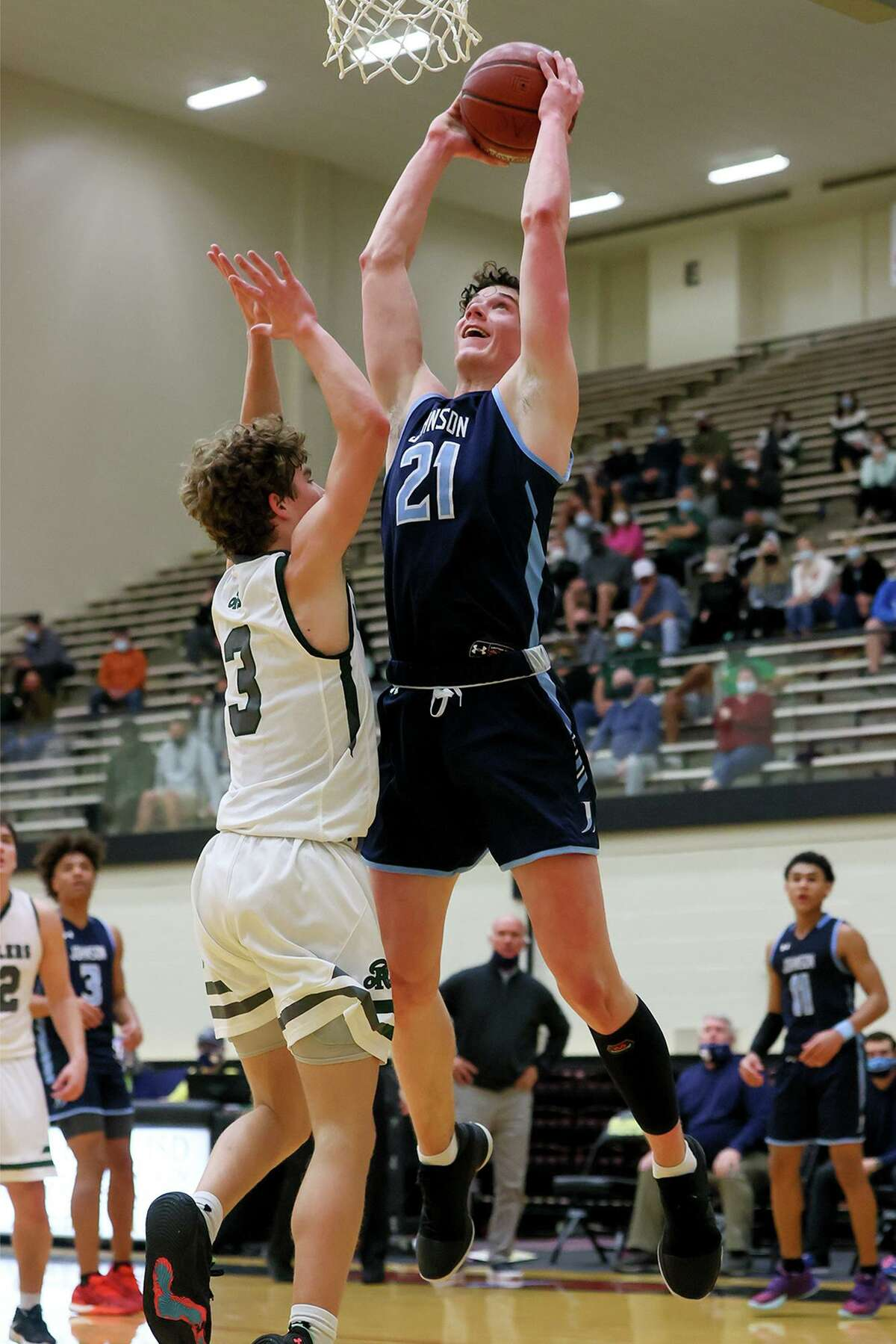 Johnson's Mitch Iden goes up for a basket over Reagan's Trey Thompson during their District 28-6A boys basketball game at Littleton Gym on Saturday, Jan. 23, 2021. Johnson beat Reagan 66-46.