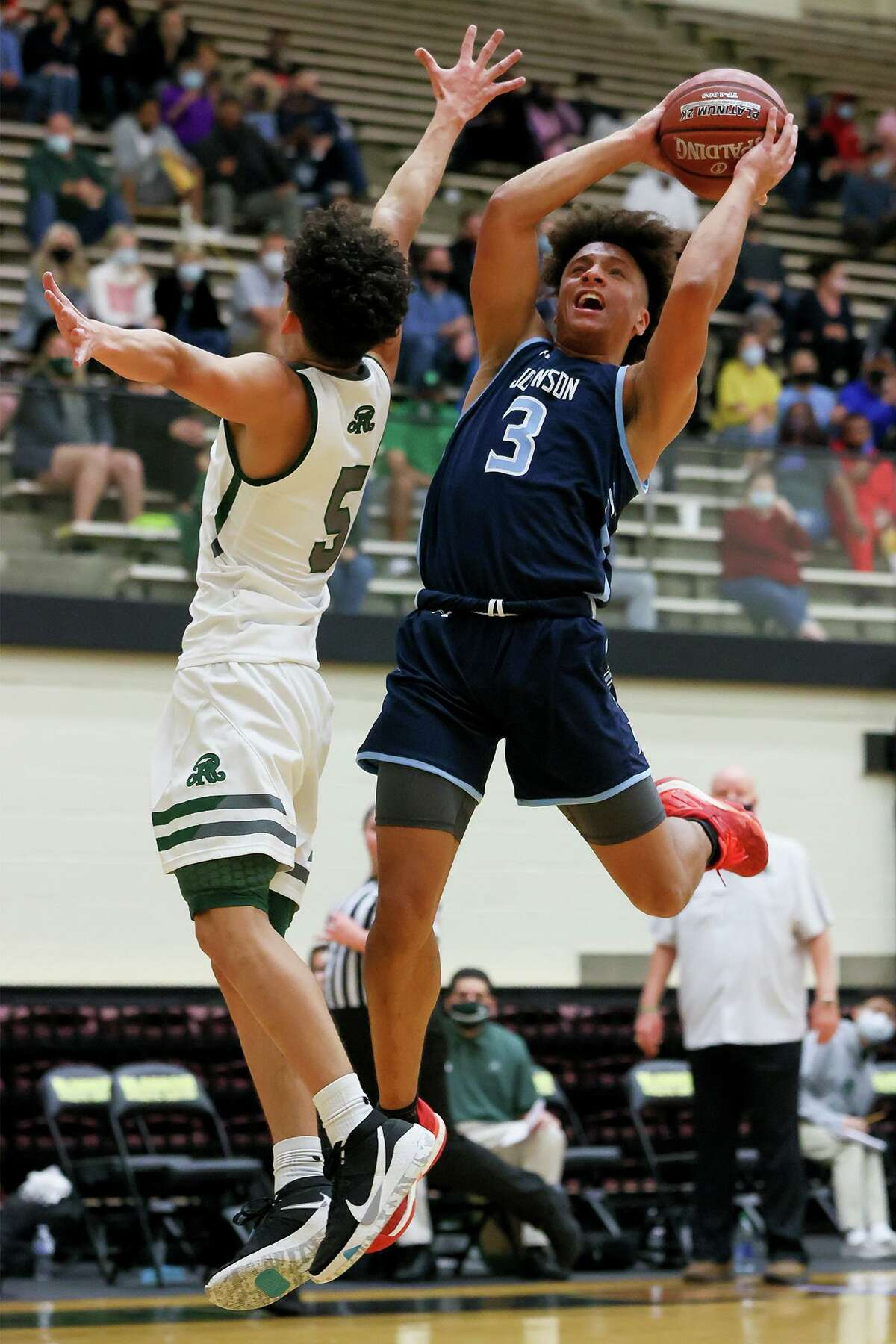 Johnson's Shane Johnson, right, shoots around Reagan's Keith Davis during their District 28-6A boys basketball game at Littleton Gym on Saturday, Jan. 23, 2021. Johnson led the Jaguars with 17 points to help them beat Reagan 66-46.