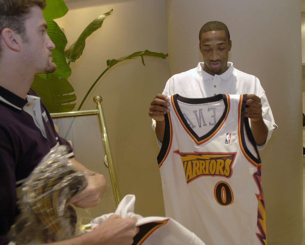 Gilbert Arenas checks out his new shirt with Ron Rogers of the Warriors' staff before the Golden State Warriors' introduction of their draft picks in Oakland, Calif. on June 28, 2001.