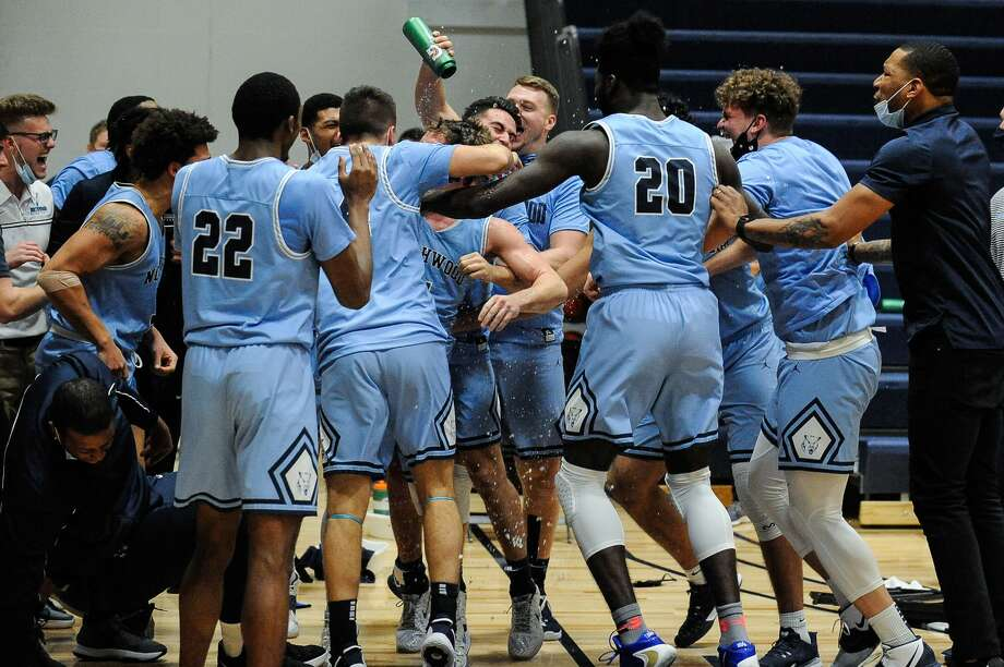 Northwood's men's basketball team swarms Jack Ammerman after he sank a buzzer-beating 3-pointer to give the Timberwolves a 67-66 win over Wayne State on Saturday, Jan. 23, 2021. Photo: Adam Ferman/for The Daily News / ADAM FERMAN