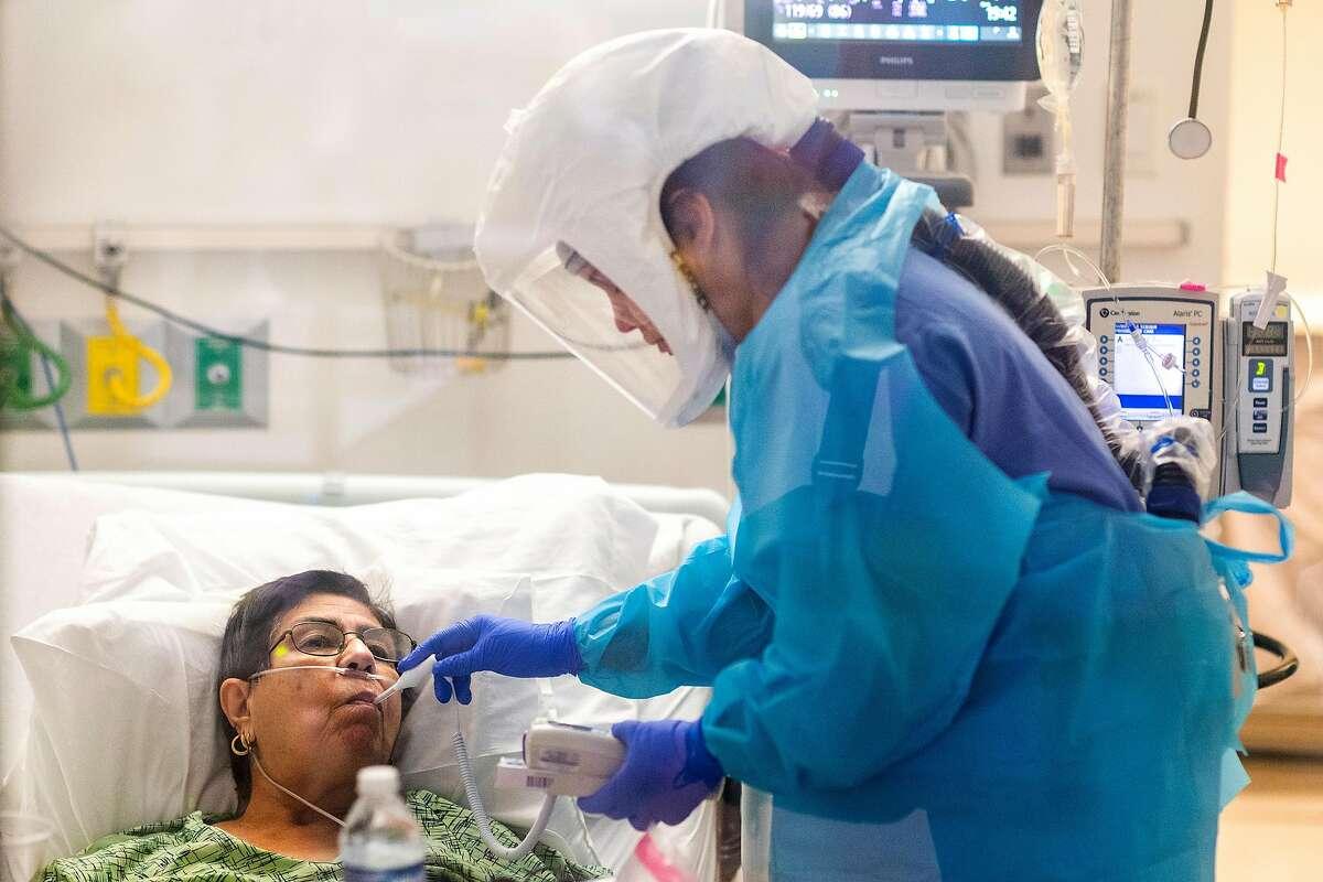 Nurse Cassie Barber checks the temperature of Carmelita Martinez, 75, of Salinas inside a COVID unit at Salinas Valley Memorial Hospital.