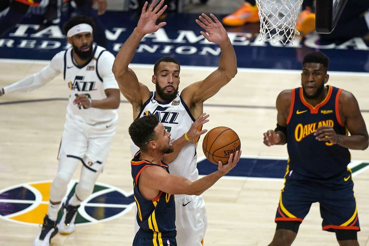 Golden State Warriors guard Stephen Curry, foreground, goes to the basket as Utah Jazz center Rudy Gobert, center rear, defends during the first half of an NBA basketball game Saturday, Jan. 23, 2021, in Salt Lake City. (AP Photo/Rick Bowmer)