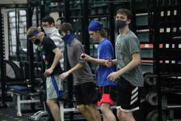 Evart boys basketball players work out in the weight room on Thursday. (Pioneer photo/John Raffel)