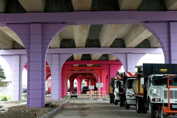 Workers place a beam on the Elysian Viaduct, with it's colorful new columns, over I-10 East Freeway, Thursday, June 25, 2020, in Houston.