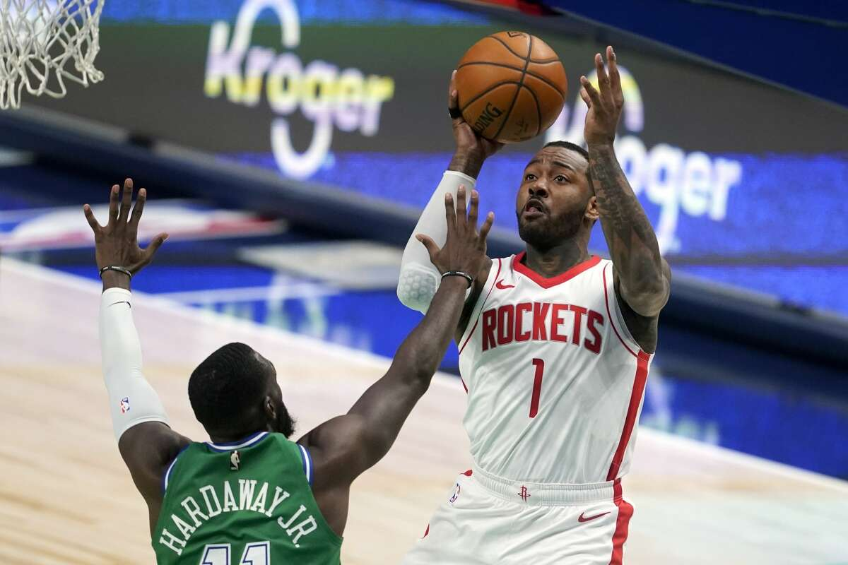 Dallas Mavericks forward Tim Hardaway Jr. (11) defends against a shot by Houston Rockets guard John Wall (1) during the second half of an NBA basketball game in Dallas, Saturday, Jan. 23, 2021. (AP Photo/Tony Gutierrez)