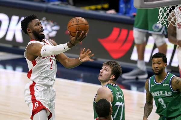 Houston Rockets guard David Nwaba (2) leaps to the basket for a shot as Dallas Mavericks' Luka Doncic (77) and Trey Burke (3) watch during the second half of an NBA basketball game in Dallas, Saturday, Jan. 23, 2021. (AP Photo/Tony Gutierrez)