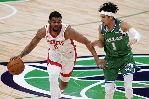 Houston Rockets guard Mason Jones (9) brings the ball up as Dallas Mavericks guard Tyrell Terry (1) defends during the second half of an NBA basketball game in Dallas, Saturday, Jan. 23, 2021. (AP Photo/Tony Gutierrez)