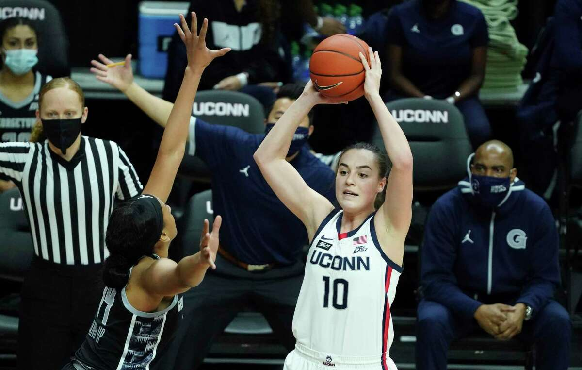 UConn's Nika Muhl (10) looks to pass while defended by Georgetown's Jillian Archer (14) on Saturday in Storrs.
