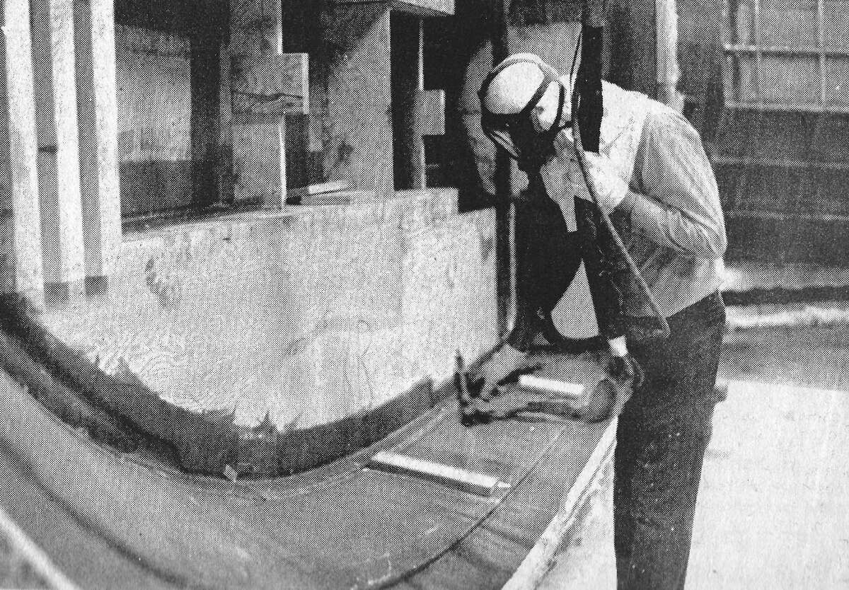 An employee of Century Boat Company wears a full head mask as protection against toxic ingredients in the urethane foam spray as he works on the interior of a boat hull for the purposes of strength, flotation and soundproofing of the hull. The photo was originally published in the Jan. 23 issue of the News Advocate. (Manistee County Historical Museum photo)