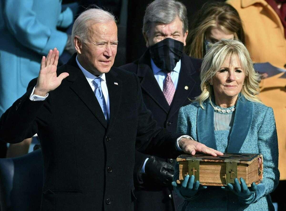 Joe Biden, flanked by Jill Biden, takes the oath of office as the 46th president Jan. 20, 2021.