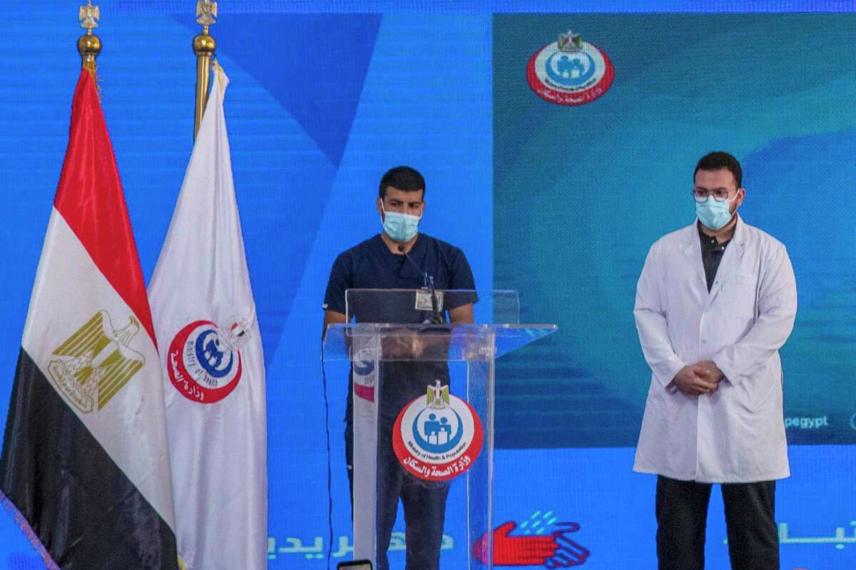 Nurse Ahmed Hamdan Zayed, left, and Dr. Abdel Menoim Selim, the first two Egyptians to receive the Sinopharm China-made COVID-19 vaccine, stand on a stage to answer questions during a press conference, at the Abu Khalifa Hospital in Ismailia, 120 km (75 miles) east of Cairo, Egypt, Sunday, Jan. 24, 2021.