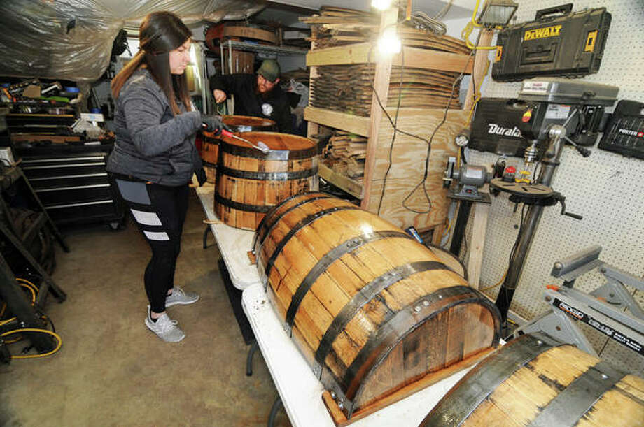 Faith and Ryan Jenkins apply finish to their creations at Second Hand Barrels in Godfrey. The business has grown so much that in March it will move into a commercial facility on Stanka Lane in Godfrey,