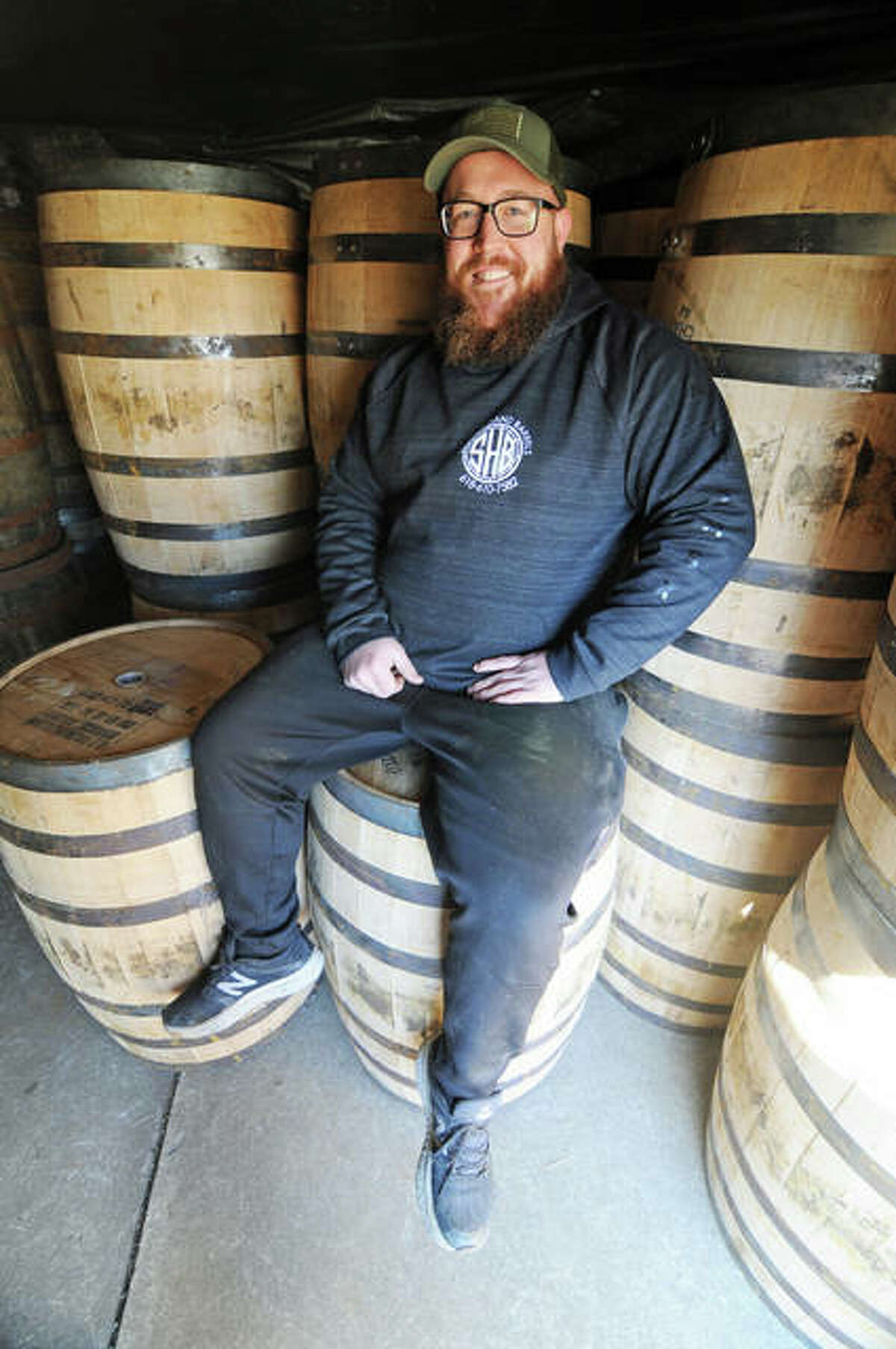 Ryan Jenkins, the owner of Second Hand Barrels in Godfrey, sits amid his supply of white oak barrels waiting to be transformed.