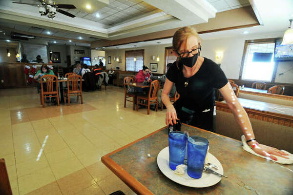 "Christina Reynolds cleans a table at the Olive Branch Cafe in Jerseyville, which has reopened under Region 3 COVID guidelines. ""It's exciting that we are getting closer and everybody will be safe again and able to enjoy life,"" said Jeni Nape at the restaurant."