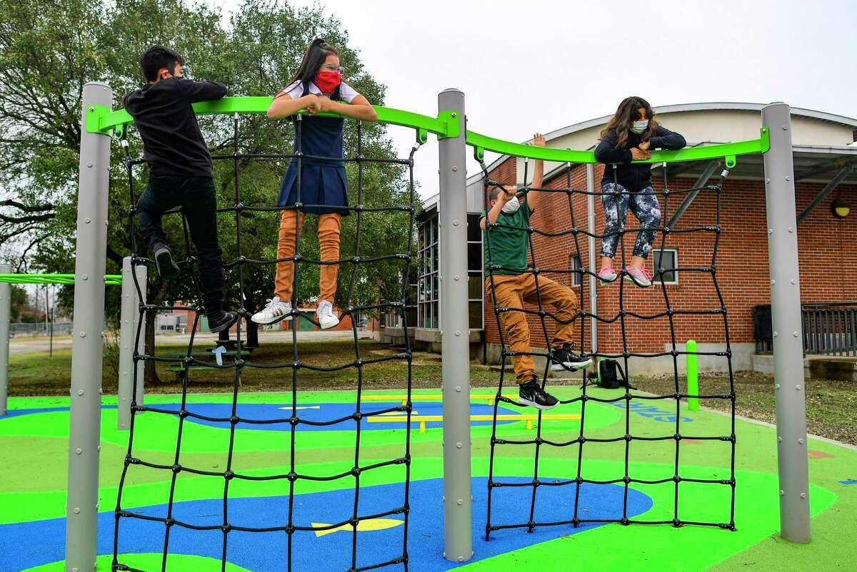 Elias Ochoa, from left, his sister Evelyn Ochoa, Kobe Salazar and Savannah Pierce play on a new ninja-style playground at Huppertz Elementary School on Thursday, Jan. 21, 2021. The playground was funded through a Texas Education Agency grant.