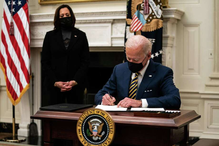 President Joe Biden signs executive orders during an event at the White House in Washington on Friday, Jan. 22 as Vice President Kamala Harris looks on. Photo: Anna Moneymaker /New York Times / NYTNS