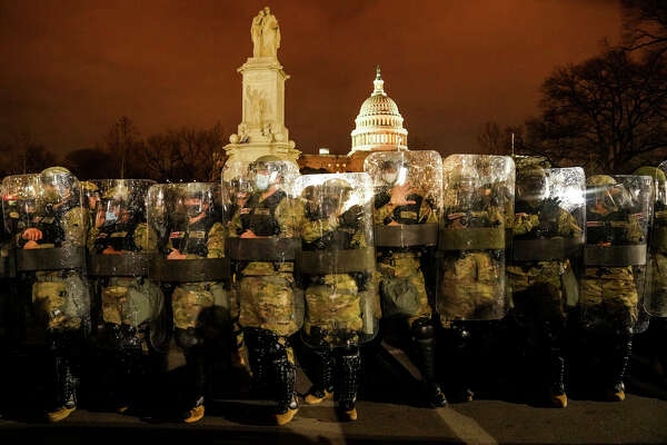 National Guard members stand outside the Capitol after a day of rioting.