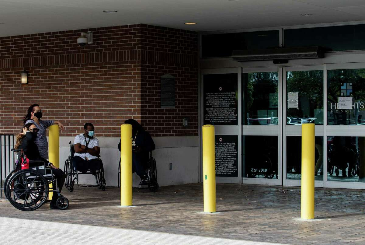 Patients stay outside the Heights Hospital, which filed for bankruptcy Monday, Jan. 18, 2021, in Houston. Medical staff and patients were locked out without any notice.