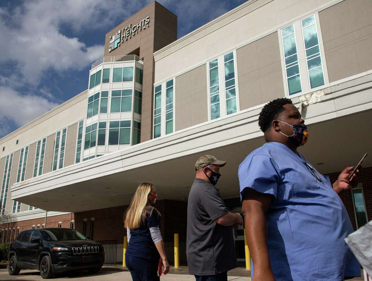 Medical staff and patients stand outside the Heights Hospital, which filed for bankruptcy Monday, Jan. 18, 2021, in Houston. Medical staff and patients were locked out without any notice.