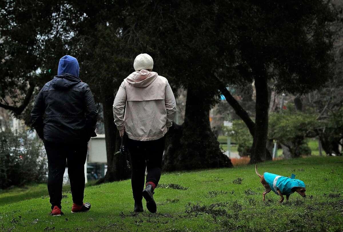 Jess Rozul (left) and Maria Zamudio walk their dog, Chuleta, as rain falls at Lake Merritt in Oakland.