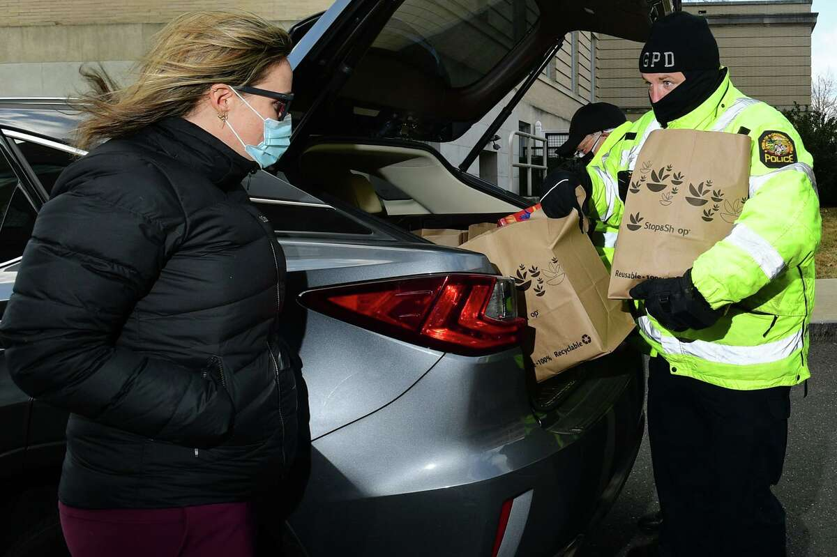 Greenwich resident Kysa Englund drops off donations to officer Thomas Huestis as The Greenwich Police Department holds a food drive at the town's Public Safety Complex Saturday, January 23, 2021, in Greenwich, Conn. The effort is to make sure all residents have food to put on the table this winter.