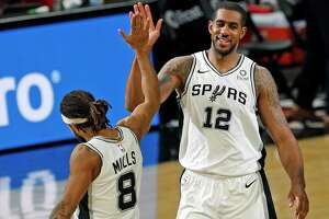 LaMarcus Aldridge #12 of the San Antonio Spurs high fives Patty Millslas Spurs defeated the Wizards 121-101. Wizards v Spurs at AT&T Center on Sunday, Jan. 24, 2021