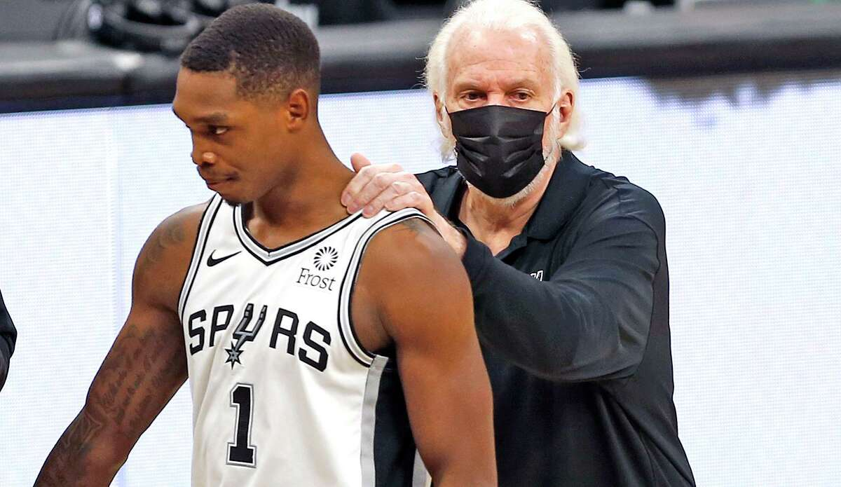 Lonnie Walker (1) of the San Antonio Spurs is greeted by coach Greg Popovich during a timeout in the game against the Wizards at the AT&T Center on Sunday, Jan. 24, 2021.