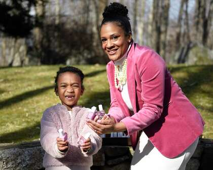 Hanadis Oakley and her daughter, Taylor Oakley, 7, show off their Chawkulit pink nail polish at their home in Stamford, Conn., Wednesday, January 20, 2021. Handis and Taylor's routine of going to the nail salon was disrupted because of COVID-19, so the two decided to start making their own nail polish. .  The start-up, which they branded as Pink Chawkulit, includes non-toxic nail polish and soon followed suit.