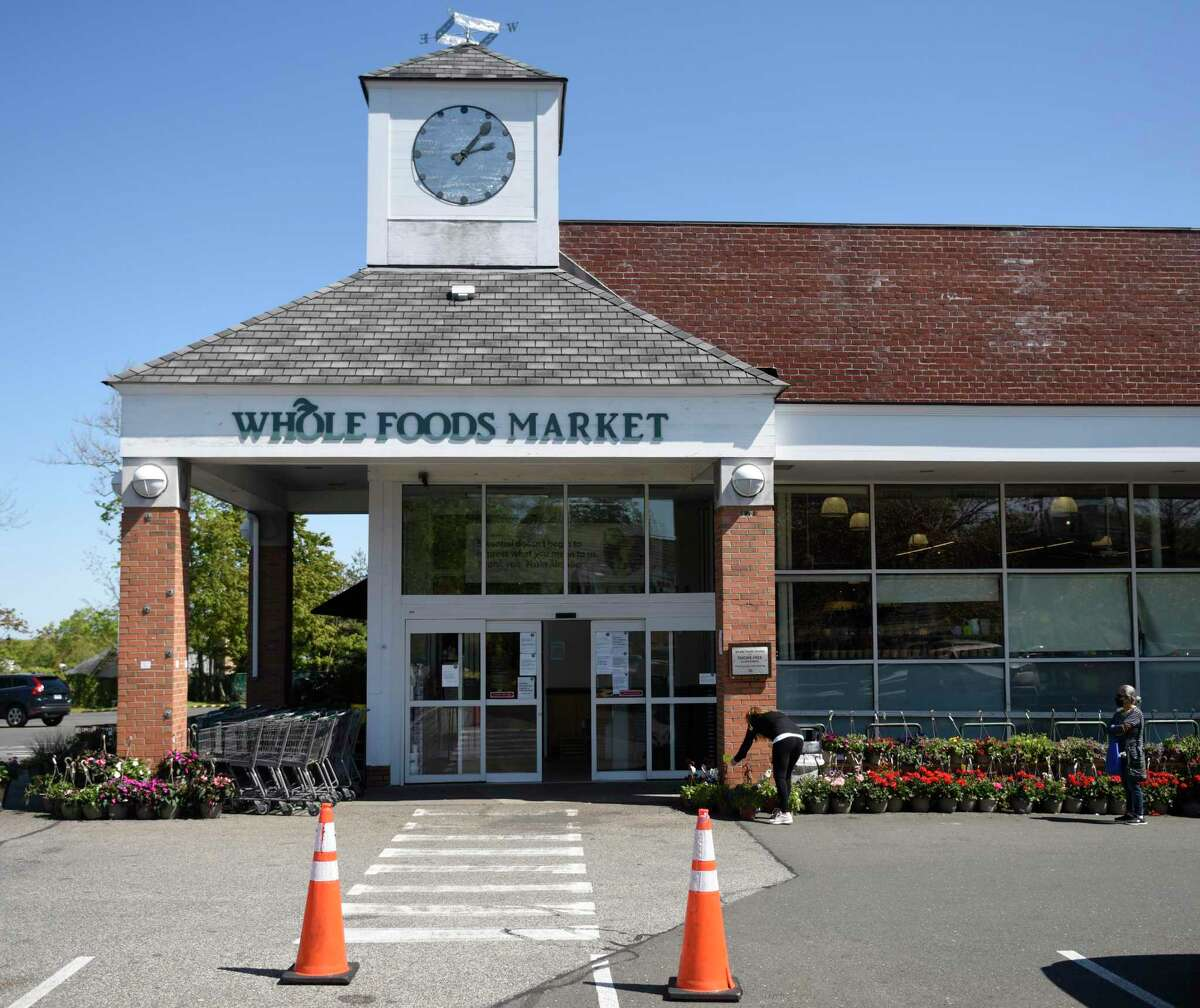 Customers wait in line to enter Whole Foods Market in Greenwich, Connecticut, Wednesday, May 13, 2020.