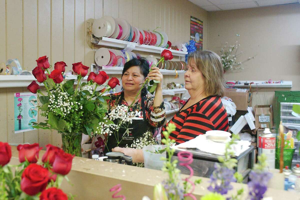 """The Enchanted Florist owner Debbie Wright, right, and employee Gloria Cervantes assemble a flower arrangement at the Pasadena business. """"This year has made what we do more meaningful,"""" Wright said."""