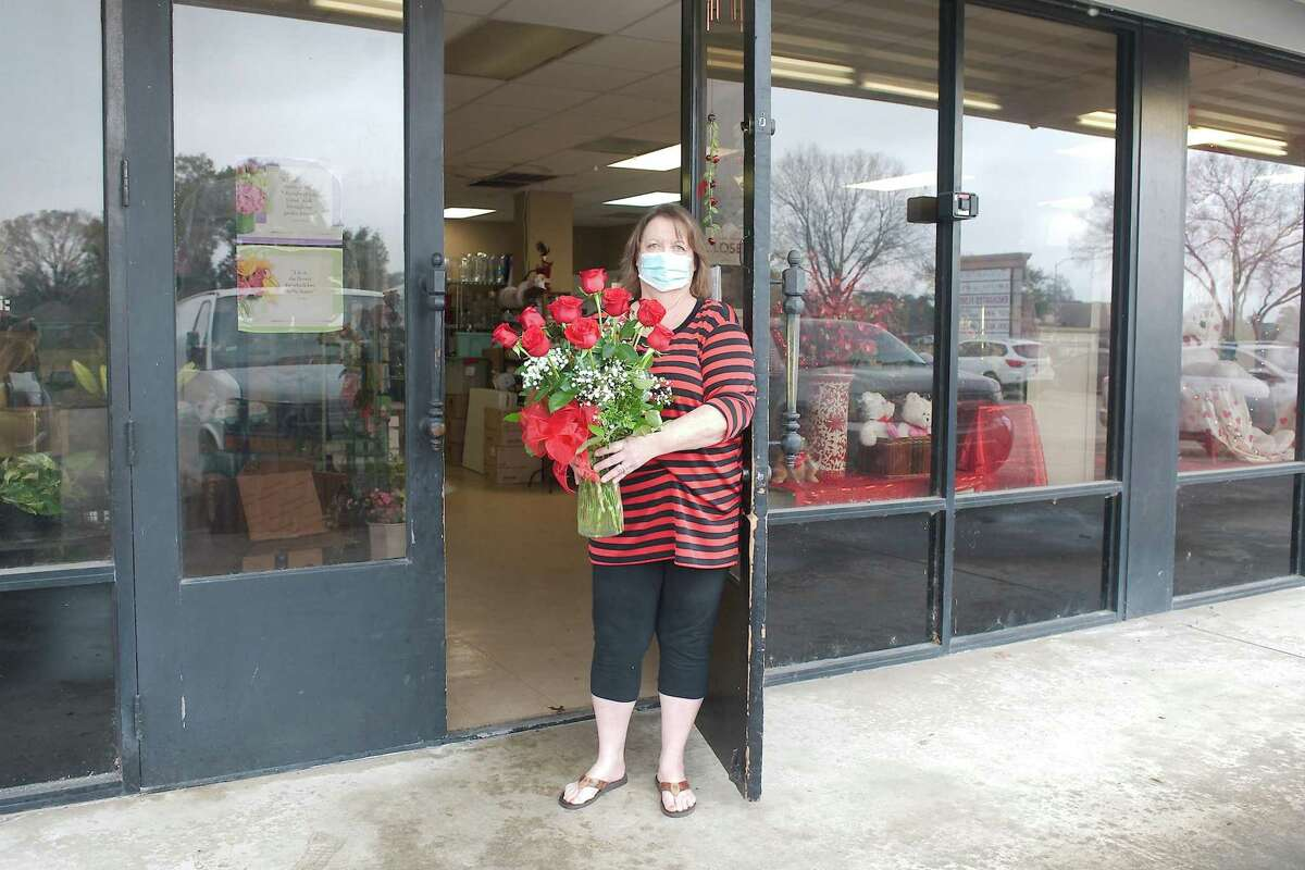 """Because her shop is closed to public entrance, Wright carries orders to customers' vehicles at The Enchanted Florist in Pasadena. """"There are more people sending flowers,"""" she says. """"That's the way they're expressing themselves because they're not able to attend; so we've been very, very busy."""""""