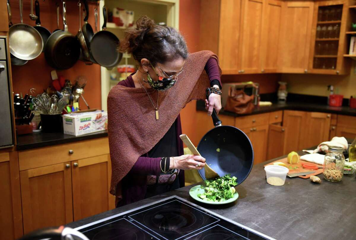 Caroline Barrett prepares a stir-fry on Tuesday, Jan. 19, 2021, at Different Drummer's Kitchen in Guilderland, N.Y. (Will Waldron/Times Union)