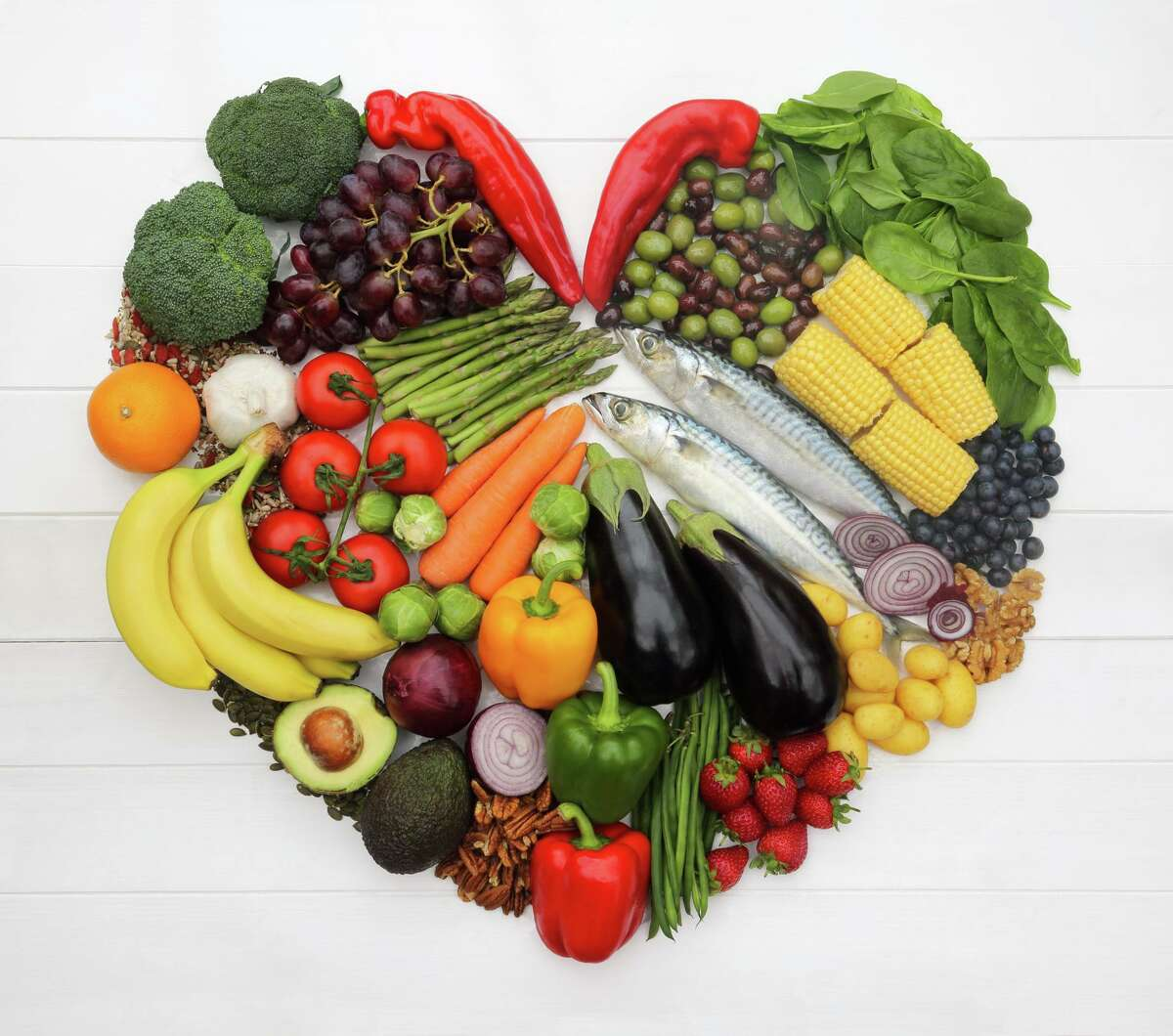 Healthy foods, which make up part of a Mediterranean diet, arranged to create a heart-shape, mackerel (fish), Ramiro peppers, bell peppers, tomatoes, nocellara and leccino olives, asparagus, carrots brussel sprouts, aubergines, red onions, avocados, green beans, spinach, corn, brocolli, potatoes, garlic, strawberries, blueberries, red grapes, bananas, orange, pecan nuts, walnuts, pumpkin seeds and mixed seeds.