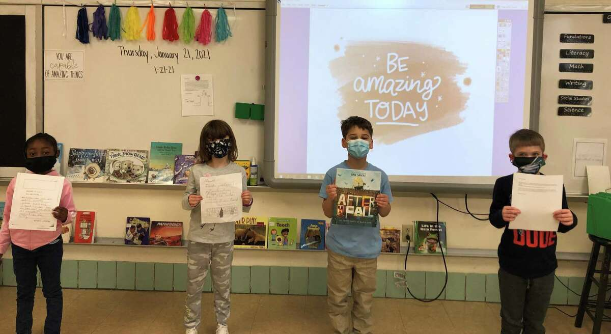 Elizabeth Shelton School first graders, left to right, Kendall Harvey, Madeline Smith, Henry Muoio and Connor Freeman show off the letters they sent to author Dan Santat. The entire class earned the chance to connect with Santat as part of winning a special contest.