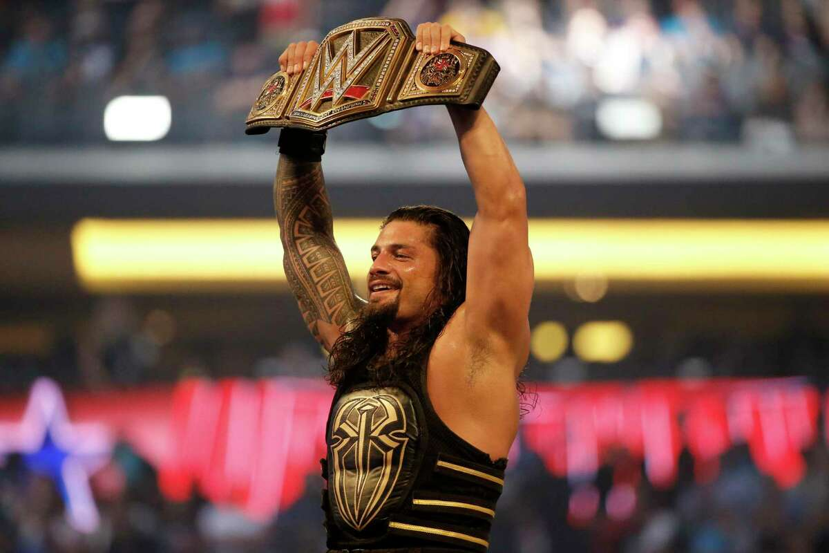 In this April 3, 2016 file photo, Roman Reigns holds up the championship belt after defeating Triple H during WrestleMania 32 at AT&T Stadium in Arlington, Texas. WrestleMania will be one of the WWE events featured on NBCUniversal's Peacock streaming service, as part of a new agreement that will see WWE Network's programming to Peacock.