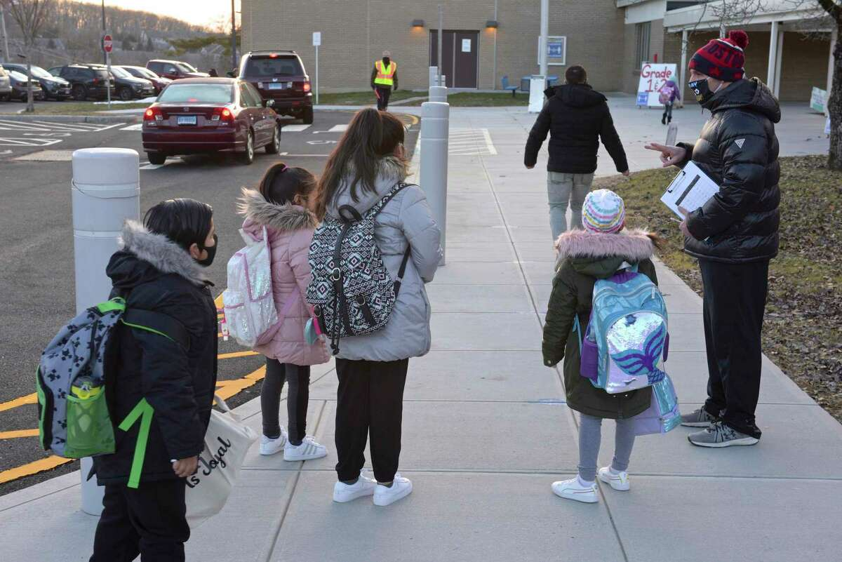 Physical Education teacher Chris Ruggiero instructs returning Stadley Rough Elementary School students where to go as they return for the first time since March of last year. Tuesday, January 19, 2021, in Danbury, Conn. Students will return fully in-person on Monday.